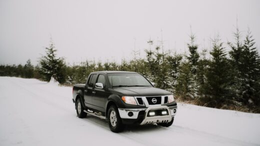 A black car driving on a snowy road Description automatically generated with low confidence